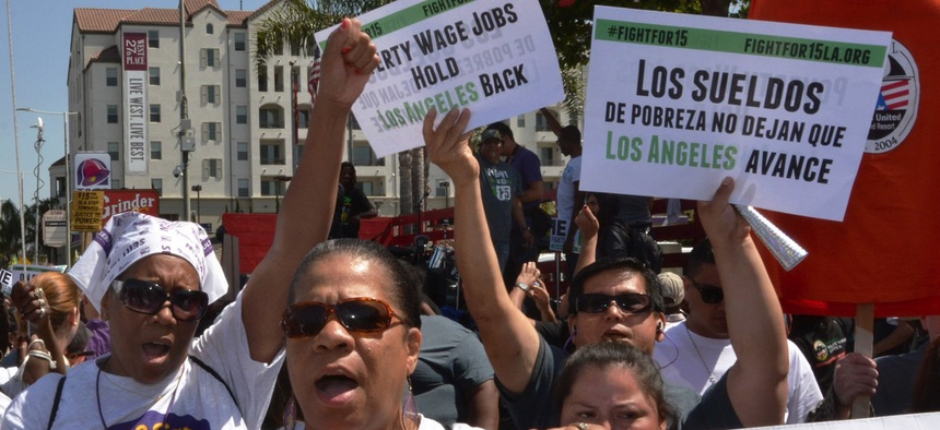Protestors shout and hold signs advocating raising the minimum wage at during a rally in Los Angeles on April 15, 2015.