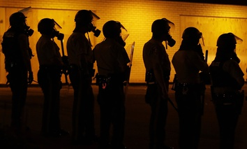 Police wait to advance after tear gas was used to disperse a crowd during a protest for Michael Brown, who was killed by a police officer on Aug. 9, in Ferguson, Mo.