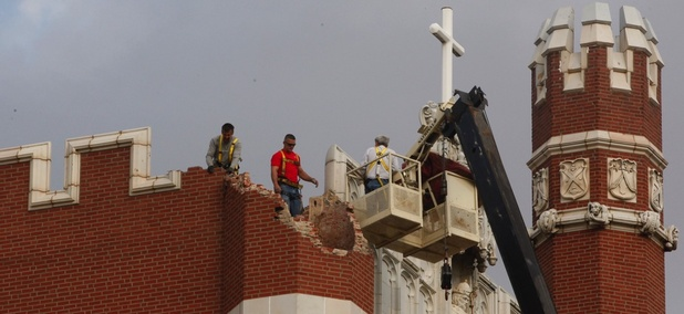 Maintenance workers inspect damage to Benedictine Hall at St. Gregory's University in Shawnee, Oklahoma, on Nov. 6, 2011. Two earthquakes in less than 24 hours caused a tower to topple and damaged the other three.