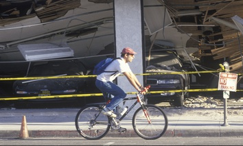 A cyclist rides by a destroyed car dealership in Santa Monica, Calif., after the Northridge earthquake in 1994.