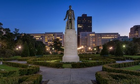 A statue and grave site of Huey Long on the grounds of the Louisiana State Capitol building at night in Baton Rouge, Louisiana.
