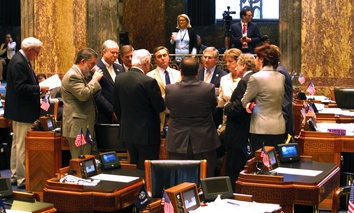 Louisiana senators meet with Senate President John Alario on the Senate floor ahead of the voting on the final day of a special legislative session on the budget and taxes, on March 9, 2016, in Baton Rouge, La.