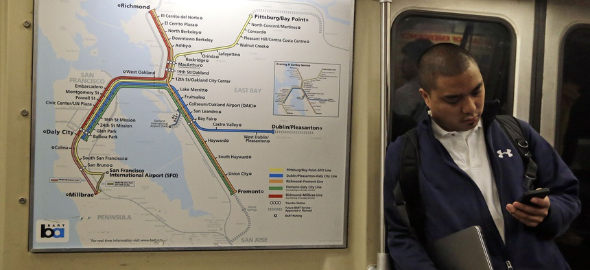 A passenger rides a Bay Area Rapid Transit train Tuesday, Oct. 15, 2013, in Oakland, Calif.