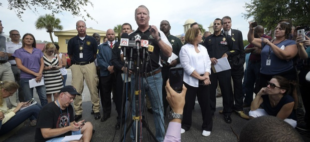 Orlando Mayor Buddy Dyer addresses reporters while flanked by members of law enforcement and community leaders during a news conference after a shooting involving multiple fatalities at a nightclub in Orlando, Fla., on Sunday.