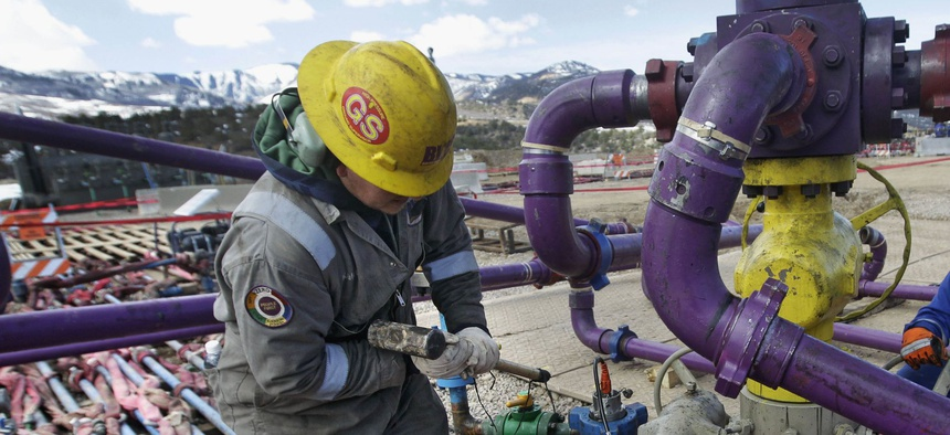 Workers tend to a well head during a hydraulic fracturing operation at an oil and natural gas extraction site, outside Rifle, on the Western Slope of Colorado.
