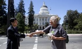 State Sen. Richard Pan (D-Sacramento) shakes hands with  Debbie Bartley near the California State Capitol in Sacramento.