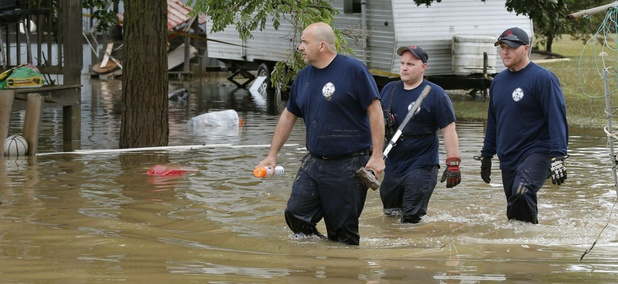 Bridgeport, W.Va., firefighters, Steve Gallo, left, and Ryan Moran, center, are joined by an unidentified co-worker as they walk through a flooded street while searching homes in Rainelle, W. Va., Saturday, June 25, 2016.