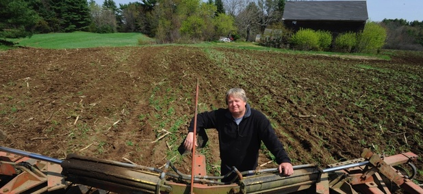 Peter Orr stands behind a harrow used to till his land on his farm in Thompson, Connecticut.