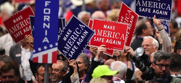 Signs are passed out to delegates during the evening session of the opening day of the Republican National Convention in Cleveland on Monday.