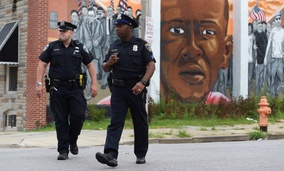 Baltimore police officers walk near a mural of Freddie Gray.
