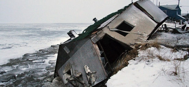 An abandoned house at the west end of Shishmaref, Alaska, sits on the beach after sliding off during a fall storm in 2005.