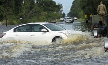 An abandoned vehicle is surrounded by water on Highway 190 near Holden, La., after heavy rains inundated the region, Sunday, Aug. 14, 2016.