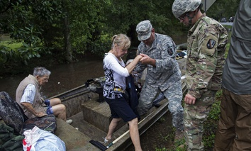 Members of the Louisiana Army National Guard rescue people from rising floodwater near Walker, La.