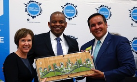 Barb Bennett, left, president/COO of Vulcan Inc., and U.S. Transportation Secretary Anthony Foxx, center, present the Smart City Challenge award to Columbus, Ohio Mayor Andrew Ginther.