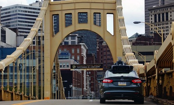 A self-driving Uber car drives across the Ninth Street Bridge in downtown Pittsburgh.