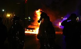 A police officer standing amid flames after riots broke out in Ferguson, Missouri on November 24, 2014.