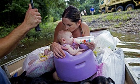 Danielle Blount and her baby wait to be rescued from floodwaters by members of the Louisiana Army National Guard near Walker, La.