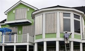 Dimitri Pinckney installs hurricane shutters in advance of Hurricane Matthew on the Isle of Palms, S.C., Wednesday, Oct. 5, 2016.
