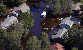 People paddle a kayak between homes flooded from Hurricane Matthew in Lumberton, N.C.