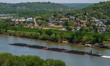 A coal barge floats past Dayton, Kentucky.