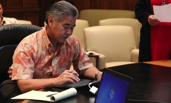 Hawaii Gov. David Ige e-signing a document.
