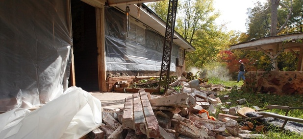 On Nov. 6, 2011 Chad Devereaux works to clear up bricks that fell from three sides of his in-laws' home in Sparks, Okla, after two earthquakes hit the area in less than 24 hours.