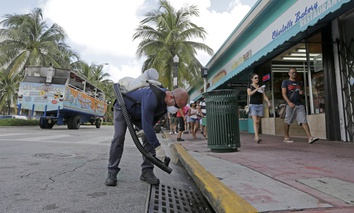 "Miami-Dade mosquito control inspector Yasser ""Jazz"" Compagines sprays a chemical mist into a storm drain, as a tour vessel passes by at left, Tuesday, Aug. 23, 2016, in Miami Beach, Fla."