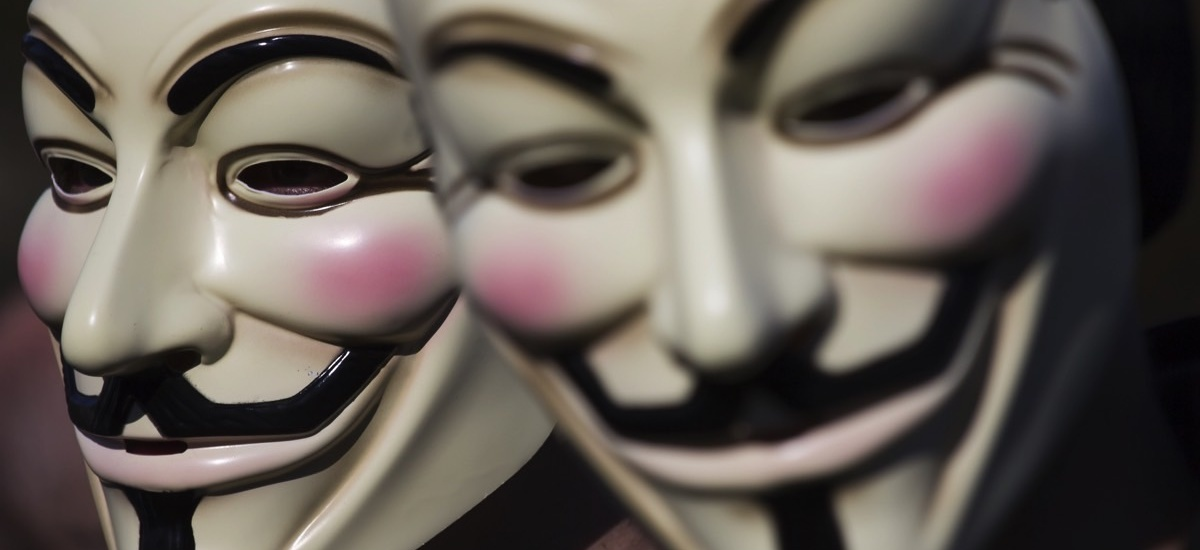 Two people wearing Guy Fawkes masks associated with the hacktivist group, Anonymous.