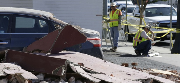 City workers at right map out the installation of fencing around earthquake damaged buildings Tuesday, Aug. 26, 2014, in Napa, Calif.
