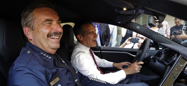 Los Angeles Police Chief Charlie Beck, left, and Mayor Eric Garcetti sit inside a police car during a news conference announcing the city's transition to green energy vehicles for its fleet in September 2015.