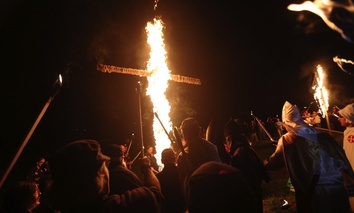 "members of the Ku Klux Klan participate in cross burnings after a ""White Pride,"" rally, in rural Paulding County near Cedar Town, Ga. in 2016."