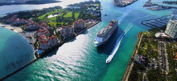 A cruise ship exits Miami into the Atlantic Ocean via the Government Cut canal.