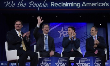 Kansas Gov. Sam Brownback waves as he is introduced for a panel discussion at the Conservative Political Action Conference (CPAC) in Oxon Hill, Md., Thursday.