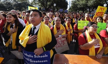 Parents, students and administrators recite the pledge of allegiance during a rally in support of school choice in Austin, Texas in January.