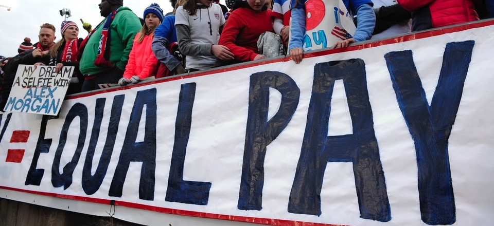 Fans stand behind a large sign for equal pay for the women's soccer team during an international friendly soccer match in April 2016.