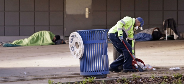 A contract worker cleans-up trash as men sleep behind him under an overpass near The Jungle encampment in Seattle.