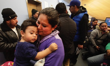 Veronica Ramirez, originally from Mexico, holds her 15-month-old son, Lora, as she waits in line to apply for a municipal identification card in New York City.