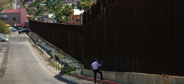 A man in Nogales, Arizona, talks to his daughter and her mother who are standing on the other side of the border fence in Nogales, Mexico.