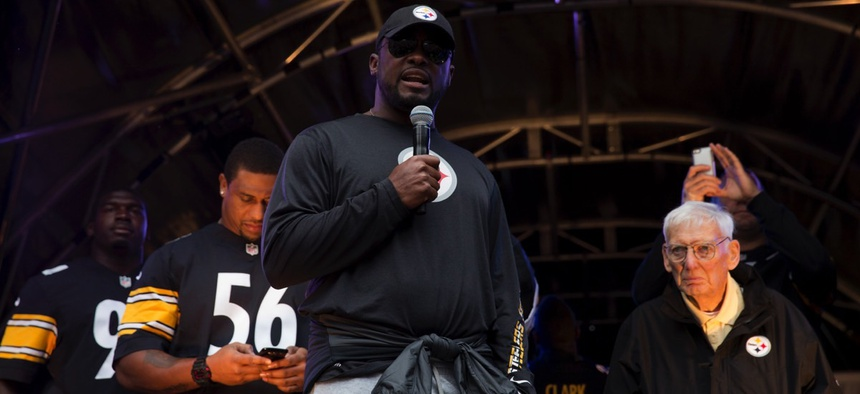 Pittsburgh Steelers head coach Mike Tomlin, center, speaks on stage flanked by the team's chairman Dan Rooney, right, during an NFL fan rally event in London in 2013.