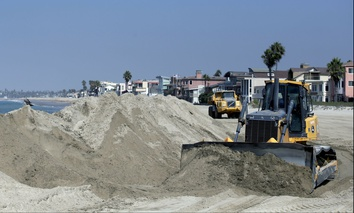 A bulldozer works to pile sand on a temporary berm to protect beach front homes on, Friday, Sept. 5, 2014, in Long Beach, Calif.