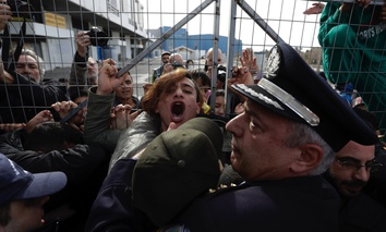 Police scuffle with Afghan migrants as they block the entrance of the Hellenikon migrant camp in Athens, Greece, in February.