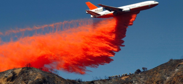 A DC-10 airplane tanker drops fire retardant to battle a wildfire in the San Gabriel Mountains in Azusa, Calif.