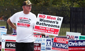 A demonstrator holds a sign against the Houston Equal Rights Ordinance outside an early voting center in October 2015.