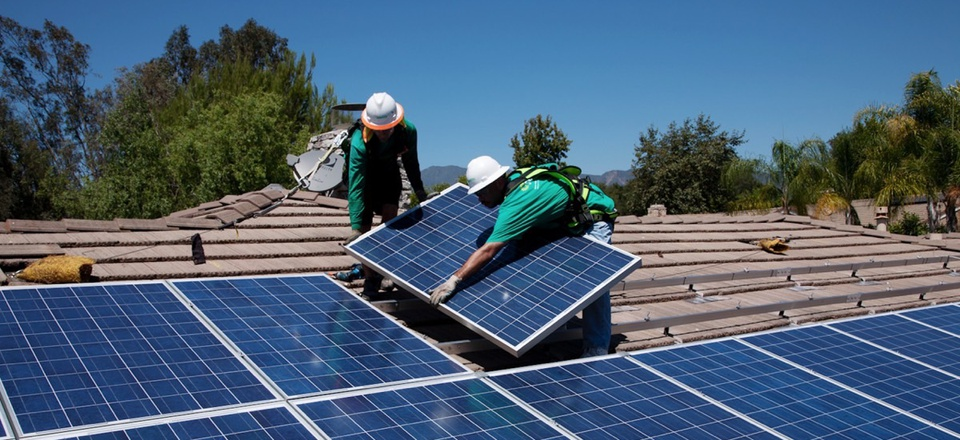 Two workers install solar panels on home in Oak View, Southern California.