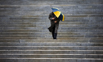 A man shields himself from the rain as he walks down the steps of the Pennsylvania state Capitol, in Harrisburg, in 2014.