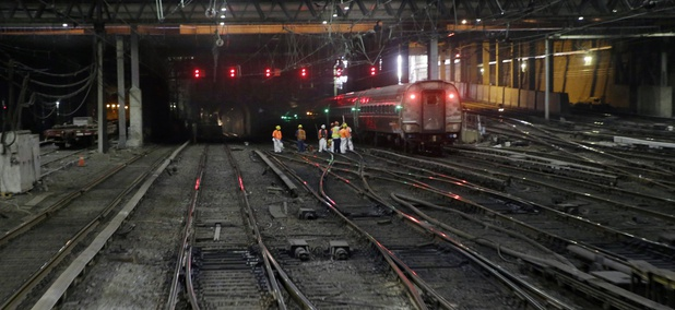 Workers near an outbound train on the tracks under New York's Penn Station on Monday, Aug. 17, 2015.