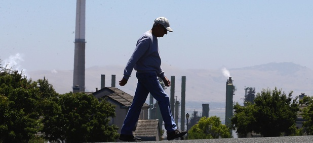 The stacks from the Valero Benicia Refinery in California are seen as a pedestrian walks in a nearby neighborhood.