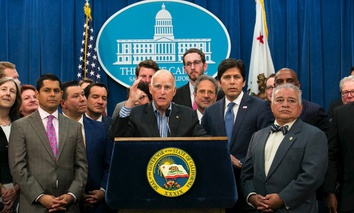 Gov. Jerry Brown, center, flanked by lawmakers from both sides of the aisle, speaks of the passage of a pair of climate change measures on Monday in Sacramento, Calif.