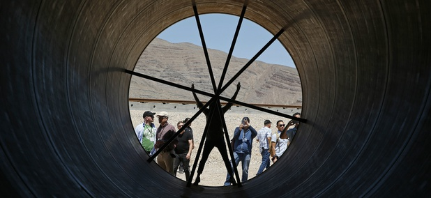 People stand in a metal tube after a test of a Hyperloop One propulsion system, Wednesday, May 11, 2016, in North Las Vegas, Nev.