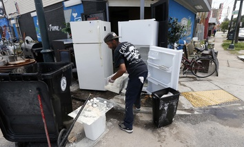 A worker throws out food from refrigerators pushed out to the curb, in the aftermath of flooding from the past weekend's rain storms, at the Treme Market and Restaurant.